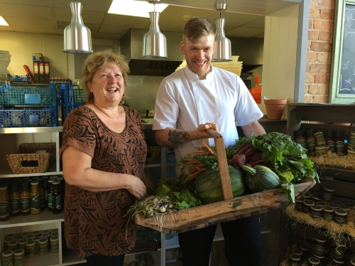 Julie MacDougall, coordinator at Future Roots Whitfield Farm, presents Dan Vaughan, head chef at The Engine Room Restaurant at Poundbury Gardens, with the latest bumper crop of vegetables grown by members of the Countrymen's Club.